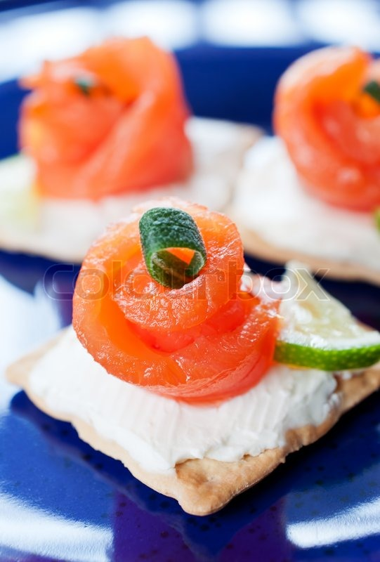 Canapes with smoked salmon and cream cheese on blue for Canape suppliers