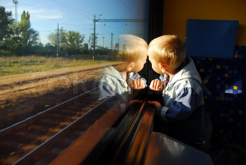 Stock image of 'Little boy looking through window. He travels on a train.'