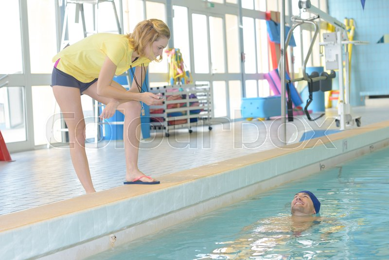 Portrait of female coach by pool at leisure center, stock photo
