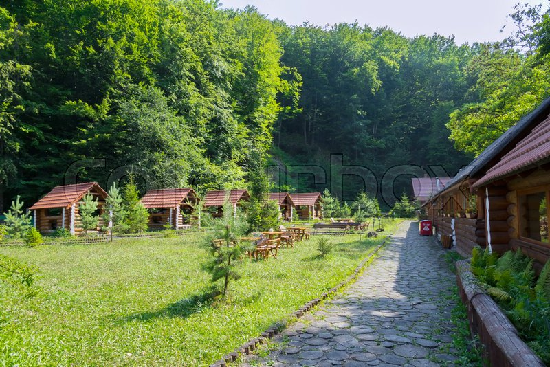 A recreation area and a picnic area with gazebos and houses of a wooden beam in a green coniferous forest, stock photo