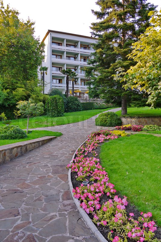 A stone path with planted flowers, tall green trees and a lawn leads to a white five-story building with balconies. place of rest, hotel, hotel, sanatorium, stock photo