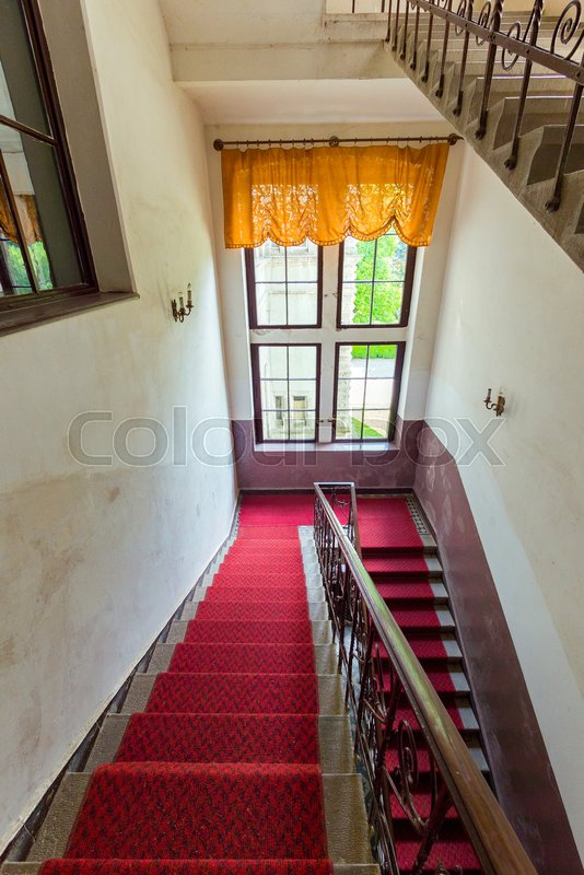 The red track is laid down the stairs down to the window with orange curtains, stock photo