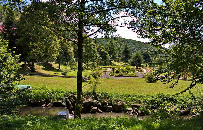 Decorative stone river rapids on the background of the beautiful green park zone of the hotel complex, stock photo