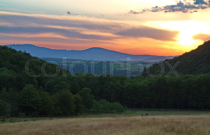 A magnificent landscape of nature in a mountainous area with the sun in the sky hiding behind the clouds and from behind them lighting the line of mountain peaks with reddish light, stock photo