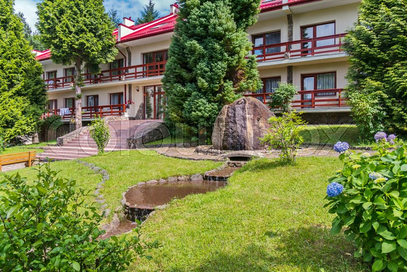 Beautiful two-storey hotel in a good location with picturesque nature with a green lawn in the courtyard and an elegant man-made waterfall flowing over the stone, stock photo