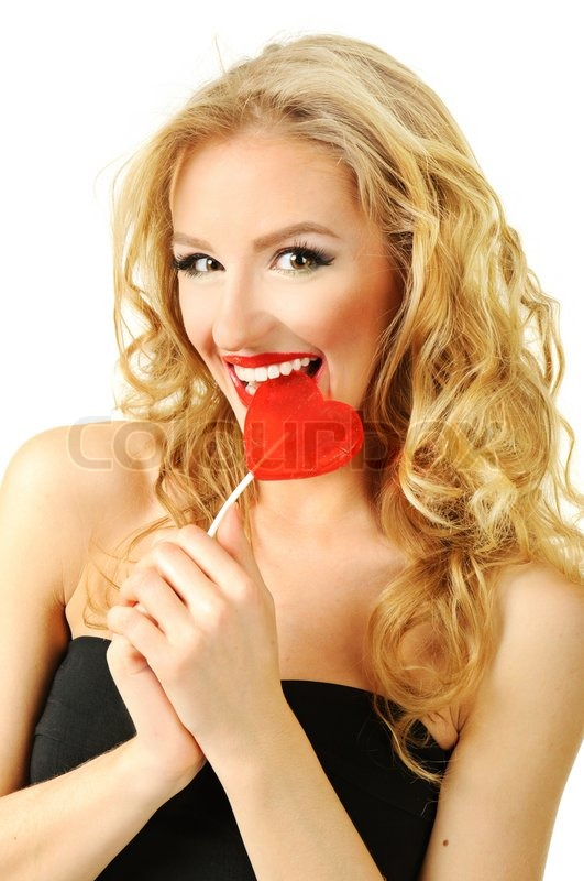 Stock image of 'Sexy valentine girl eating red heart candy'