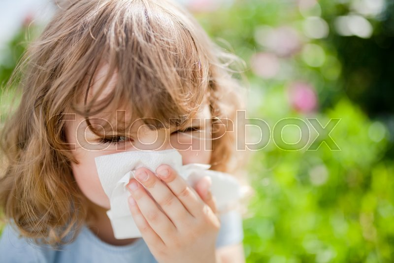 Allergy concept. Little girl is blowing her nose near blooming tree. Allergy to flowers, stock photo