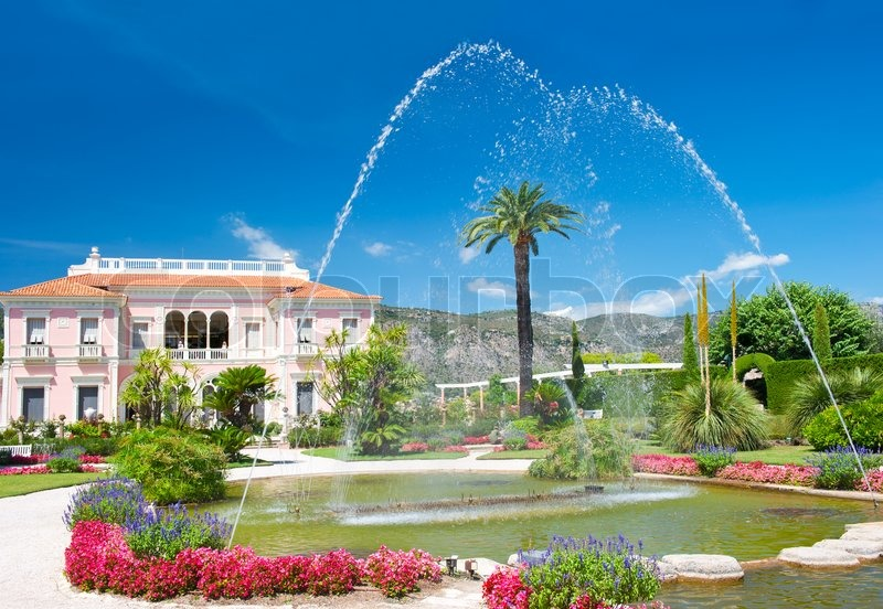 Mediterranean Garden With Fountain Colorful Flowers And Blue Sky