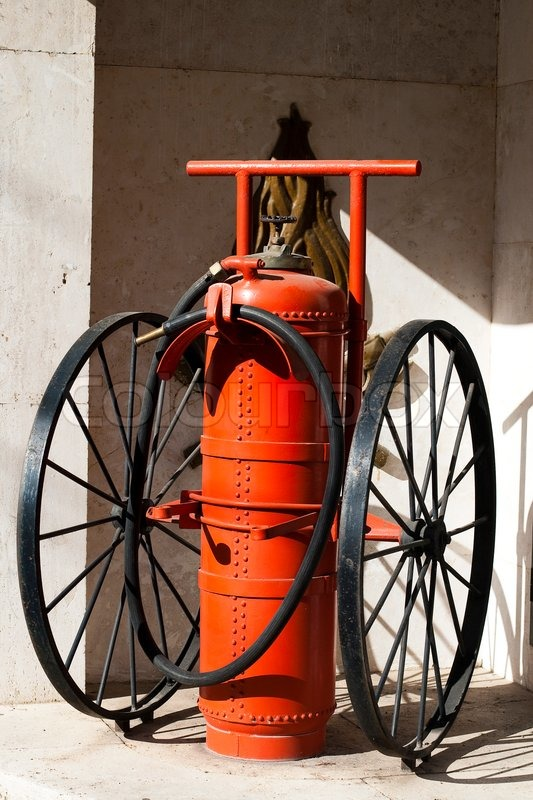 Old Big Fire Extinguisher On The Wheels Stock Photo