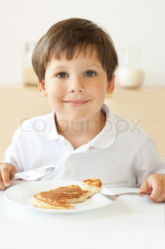 Little boy eating pancakes   Stock Photo   Colourbox