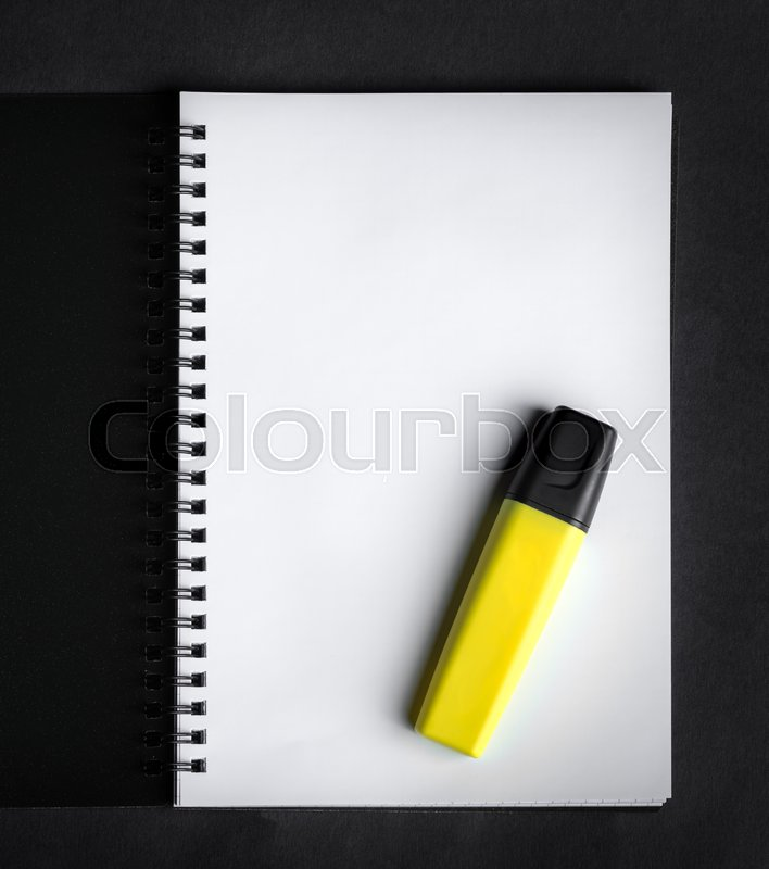 Black spiral notebook with yellow marker on the black paper background, stock photo