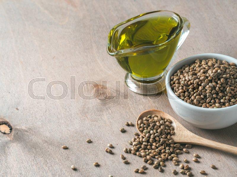 Hemp seeds and hemp oil on brown wooden     | Stock image