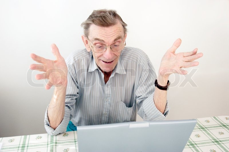 old man making happy gesture in front of computer stock photo