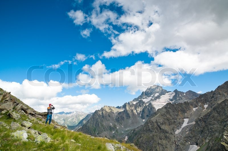 Mann wandern in den bergen mit einem fernglas stockfoto colourbox