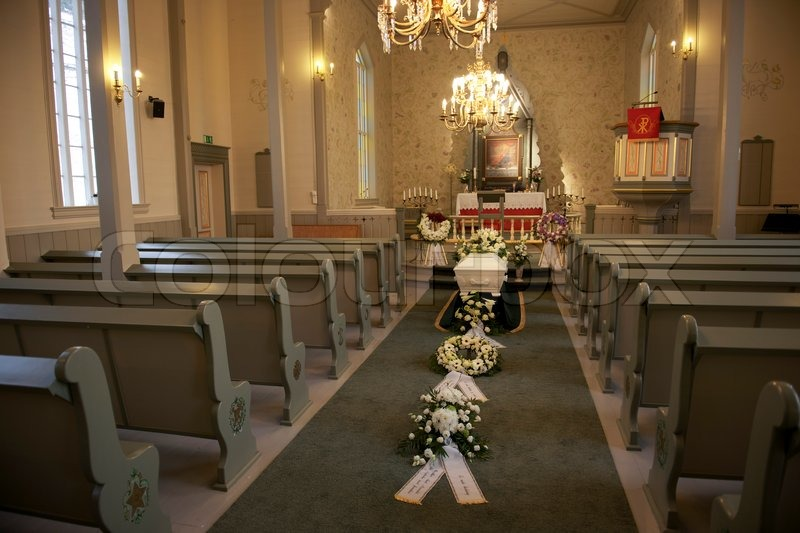 A White Casket In A Church With White Flowers Stock