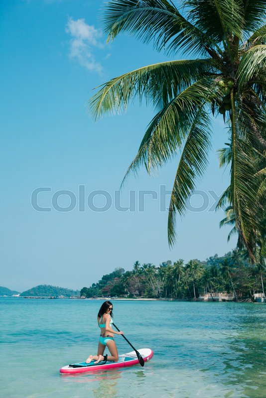 Girl on stand up paddle board on sea at tropical resort, stock photo
