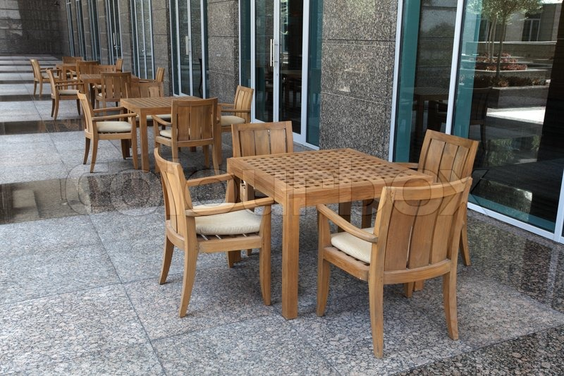 wooden tables and chairs at a cafe in the city stock photo colourbox