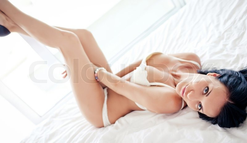 Brunette lying on bed