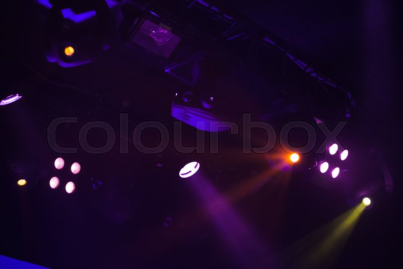Scenic spot lights with strong beams in smoke over dark background, modern stage illumination equipment, stock photo