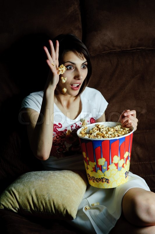 An image of woman watching TV with popcorn stock photo