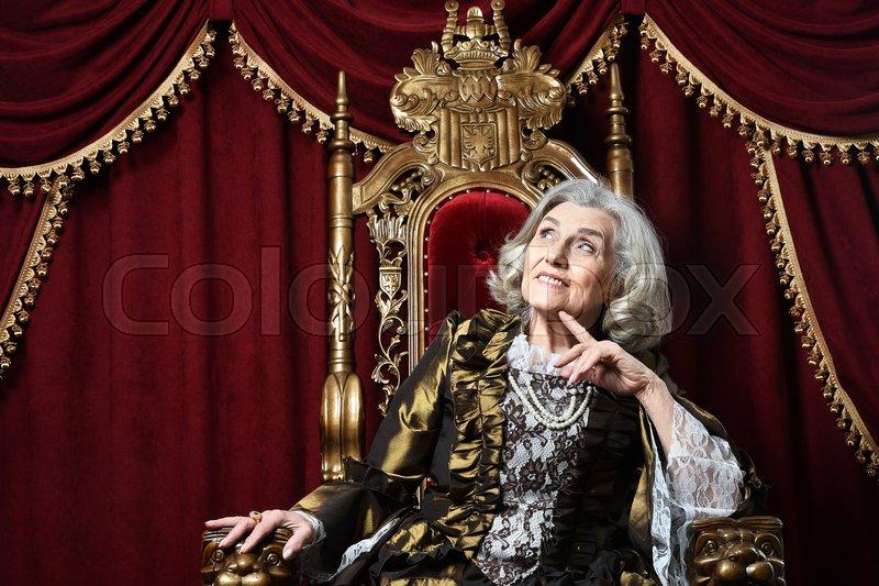 Beautiful senior woman Queen posing on throne, stock photo