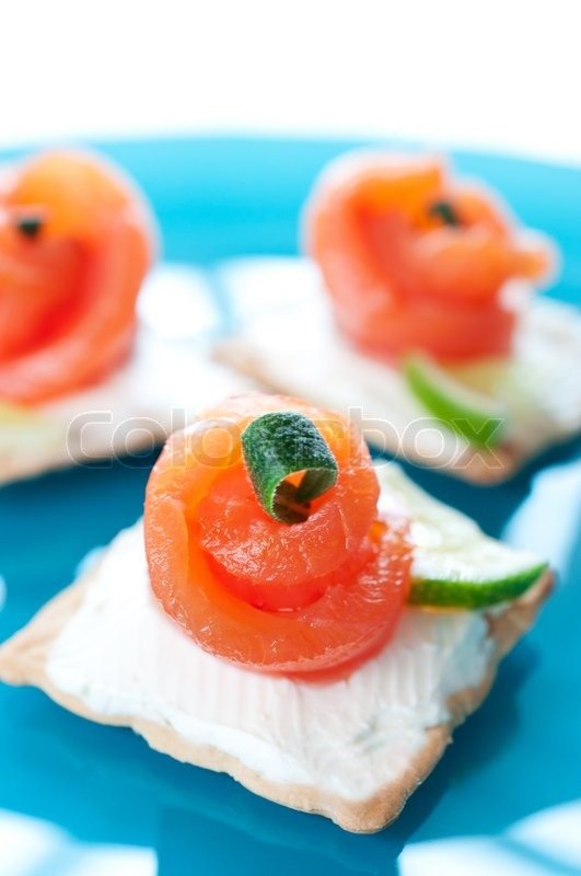 Canapes with smoked salmon and cream cheese on blue plate for Canape suppliers