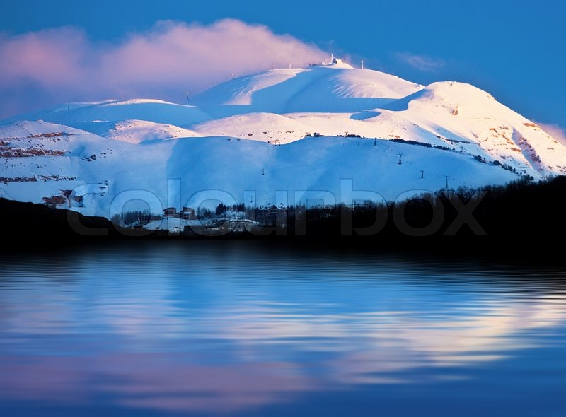 Winter landscape of high mountains covered with snow reflected in fresh lake water, pink sunset over clear blue sky, beautiful seasonal nature,panoramic wintertime image, cold weather, stock photo