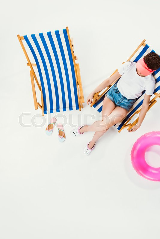 Overhead view of woman resting in beach chair isolated on white, summer vacation concept, stock photo