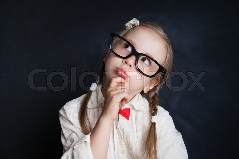 1b45d293c6 Happy smiling girl in glasses thinking and looking up on background with  copy space. Back to school