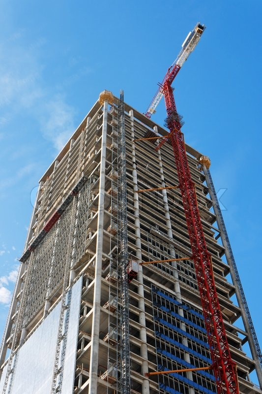 Lifting crane and high building under construction | Stock ...
