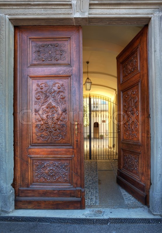 Vertical oriented image of beautiful ornate wooden door at for Beautiful wood front doors