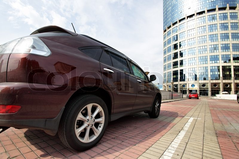 Perspective of car parking near at modern office building, stock photo