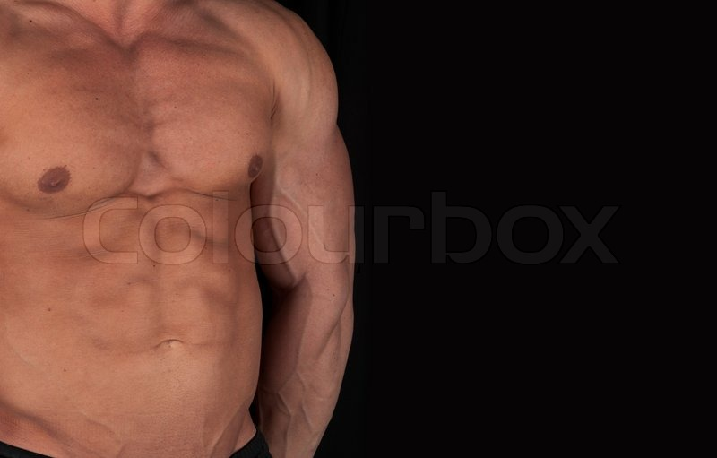 Stock image of 'Muscular male torso of bodybuilder on black background'