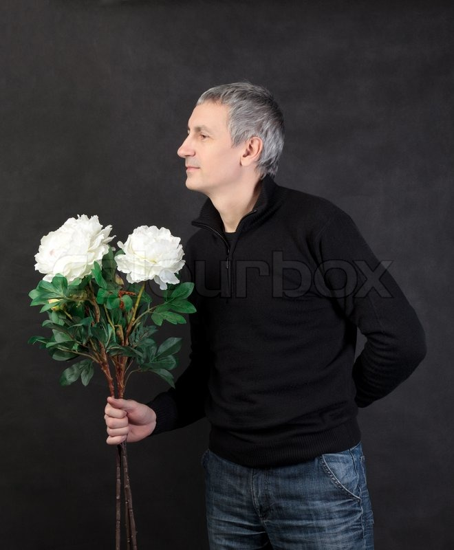 Man holding a bouquet of flowers on gray background | Stock Photo ...