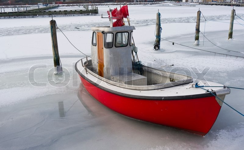 Tiny fishing boat caught by the ice in the harbor of Nyborg - Denmark | Stock Photo | Colourbox