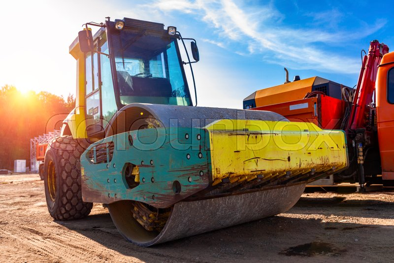 The asphalt roller is parked with other construction equipment, stock photo