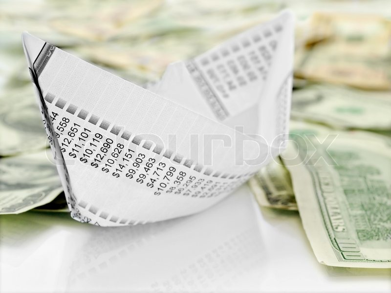 Paper Boat. Origami paper boat made from financial document on money background, stock photo