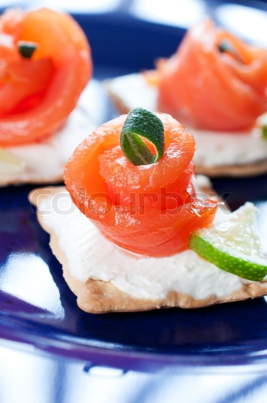 Canapes with smoked salmon on dark blue plate stock for Canape suppliers
