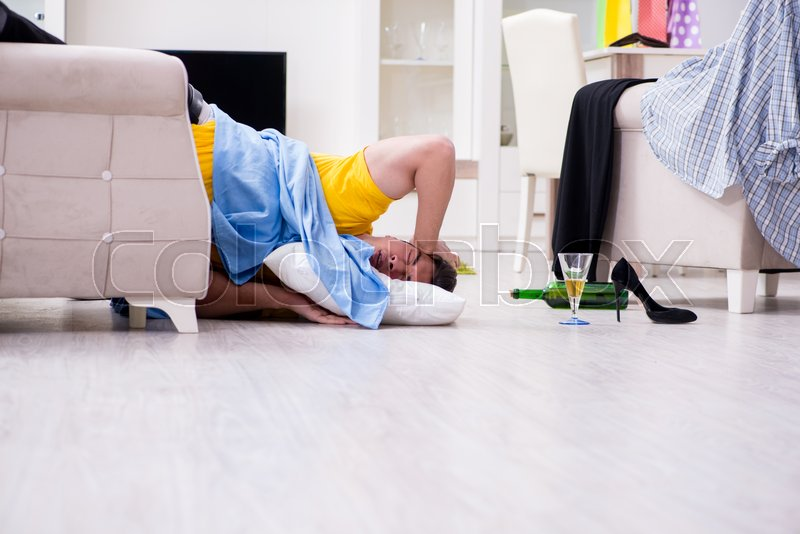 Man with mess at home after house party, stock photo