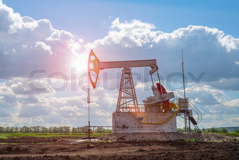 Oil and natural gas production tower in the field with a bright sun glare, stock photo