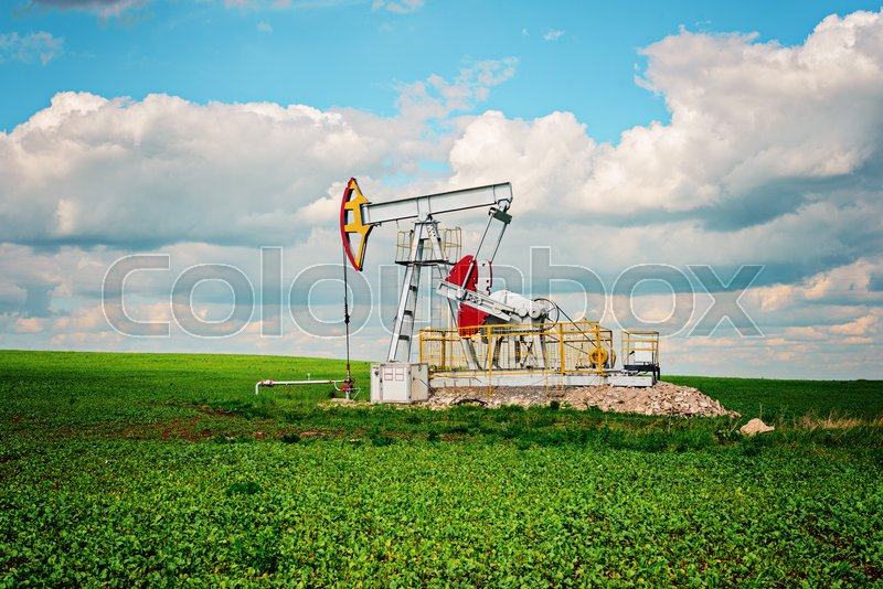 Oil pump tower in the field with green grass with blue cloudy sky, stock photo