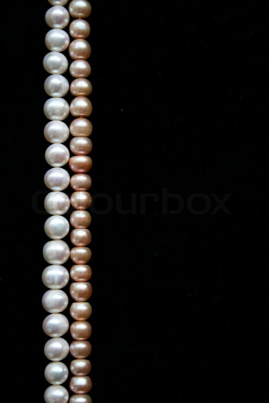 White and pink pearls on the black velvet background ...