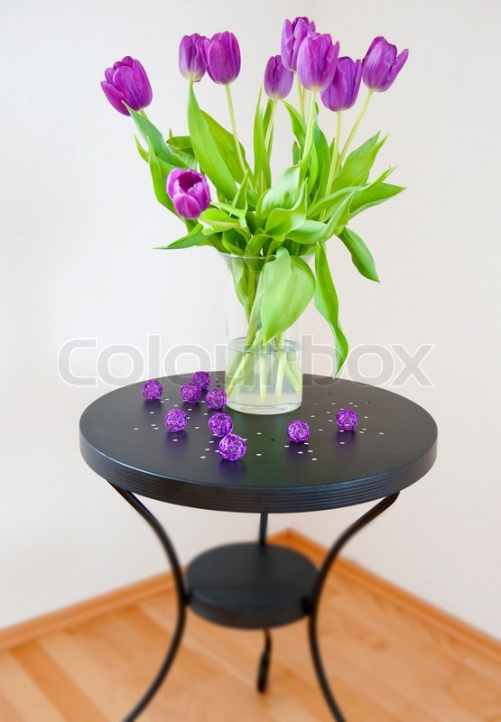 Bouquet of purple tulips in a glass vase on a black coffee for Purple coffee table