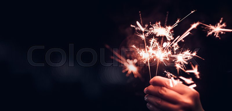 Stock image of 'Hand holding burning Sparkler blast on a black bokeh background at night,holiday celebration event party,dark vintage tone'