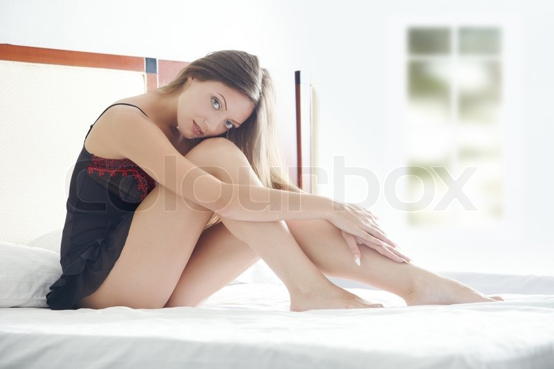 Young lady at home sits on the bed at early morning, stock photo