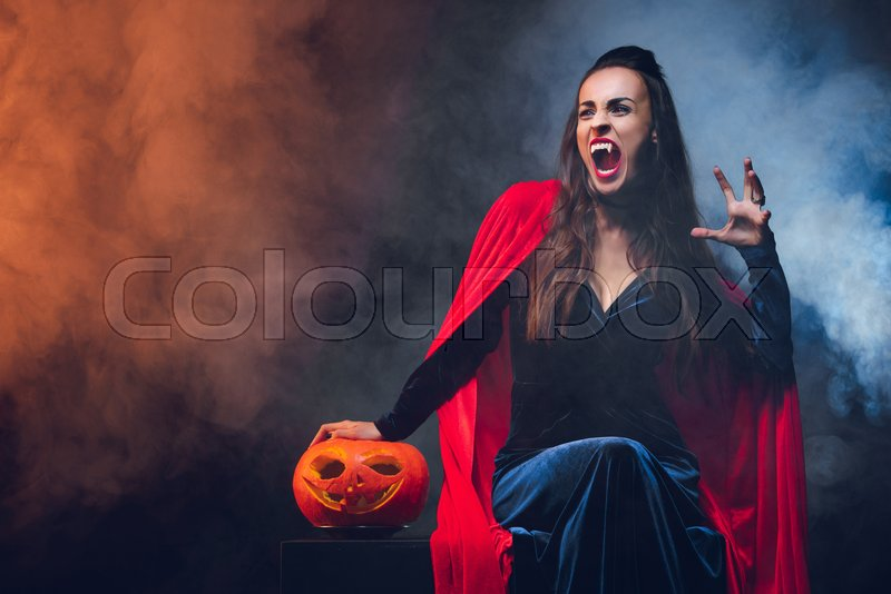Mystic woman in vampire costume holding jack o lantern on darkness with smoke , stock photo