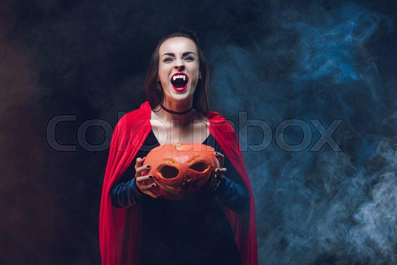 Mystic woman in vampire costume holding jack o lantern on dark background with smoke , stock photo