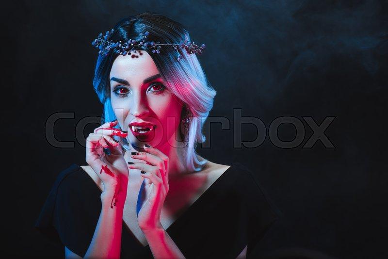 Mystic woman showing vampire teeth on dark background with smoke , stock photo