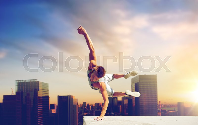 Extreme sport, parkour and people concept - young man jumping high over tokyo city background, stock photo