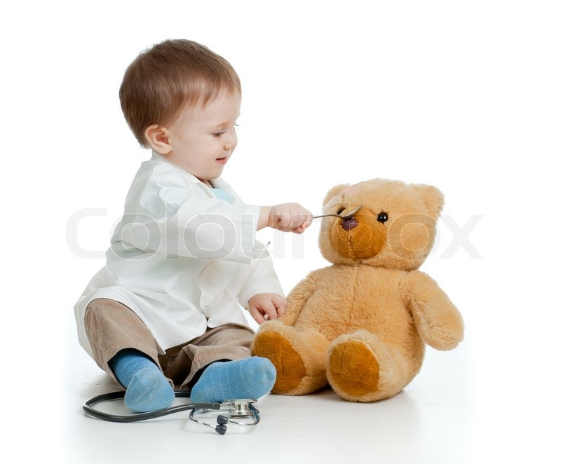 Stock image of 'Adorable boy with clothes of doctor is spoon-feeding teddy bear over white'